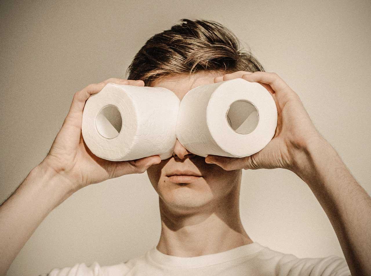 Foto eines jungen Mann, der sich Klopapierrollen wie Ferngläser vor das Gesicht hält